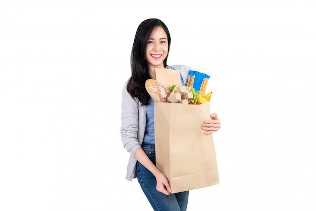 Sourire, femme asiatique, tenant un sac de papier rempli de légumes et d'épicerie Photo Premium