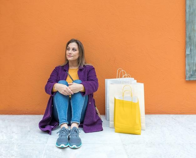 Sourire Femme Blonde D'âge Moyen Assis Sur Le Sol Avec Des Sacs à Provisions Photo Premium