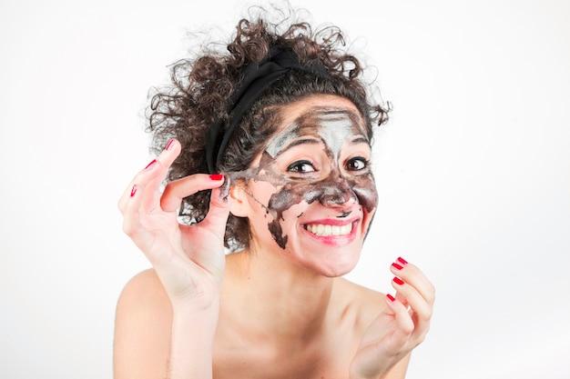 Sourire, femme, enlever, masque purifiant, visage, fond blanc Photo gratuit