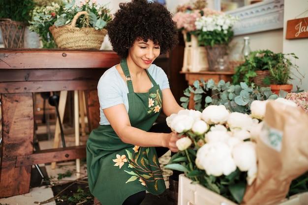Sourire femme fleuriste arrangeant des fleurs de pivoine blanches Photo gratuit
