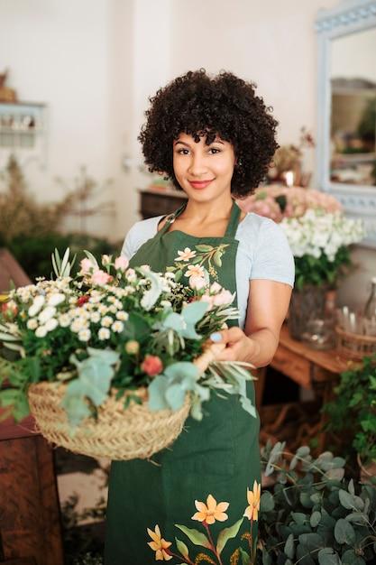 Sourire femme fleuriste tenant panier de fleurs Photo gratuit