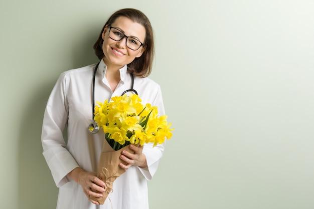 Sourire femme médecin avec bouquet de fleurs. Photo Premium