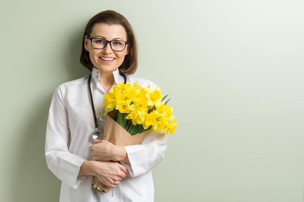 Sourire femme médecin avec bouquet Photo Premium