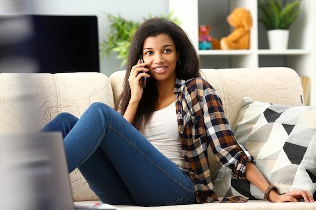 Sourire, Femme Noire, Tenir Dans La Main, Téléphone Portable, Chez Soi Photo Premium