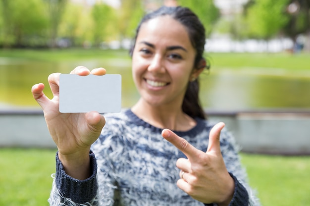 Sourire femme pointant sur une carte de visite vierge dans le parc de la ville Photo gratuit