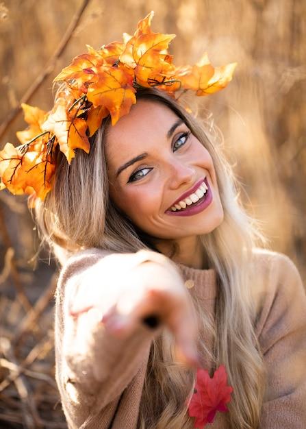 Sourire, femme, porter, érable, sec, feuilles, tiara, pointage, appareil photo Photo gratuit