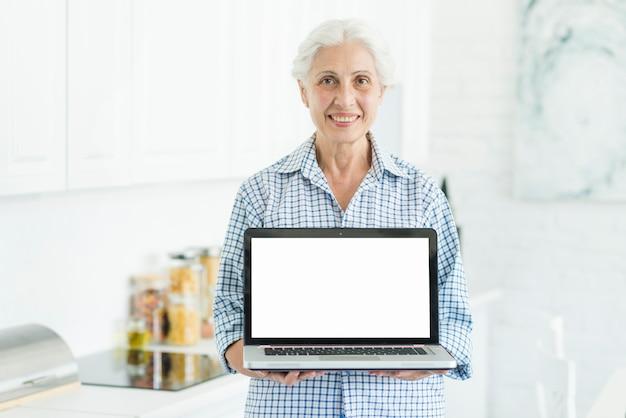 Sourire femme senior debout dans la cuisine montrant un ordinateur portable avec écran blanc Photo gratuit