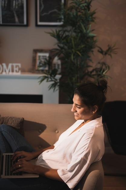 Sourire femme taper sur un ordinateur portable Photo gratuit