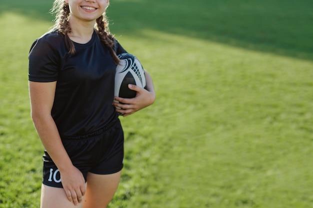 Sourire Femme Tenant Un Ballon De Rugby Photo gratuit