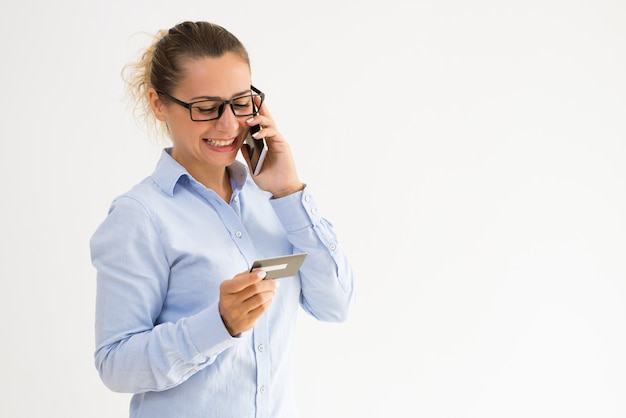 Sourire femme titulaire de la carte appelant le service de soutien Photo gratuit