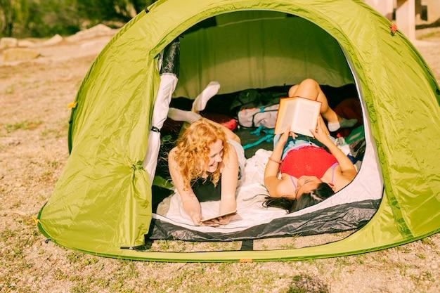 Sourire de femmes lisant des livres dans la tente Photo gratuit