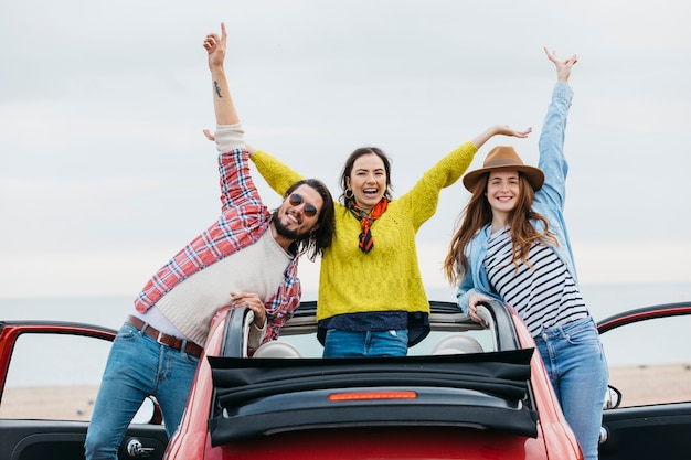 Sourire, femmes, près, homme heureux, à, haut, mains, pencher dehors, de, voiture Photo gratuit