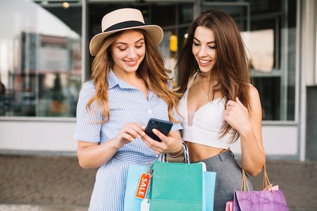Sourire des femmes regardant l'écran du smartphone Photo gratuit