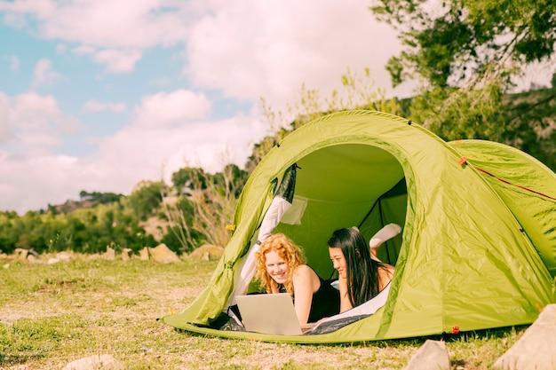 Sourire de femmes se trouvant dans une tente avec ordinateur Photo gratuit