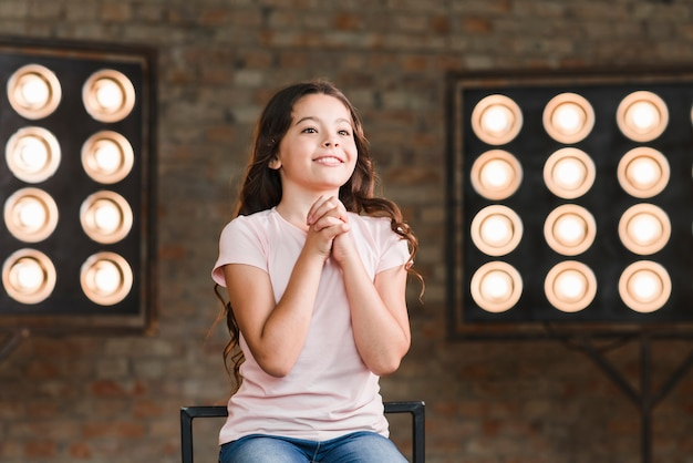 Sourire fille assise contre la lumière de la scène frappant ses mains Photo gratuit