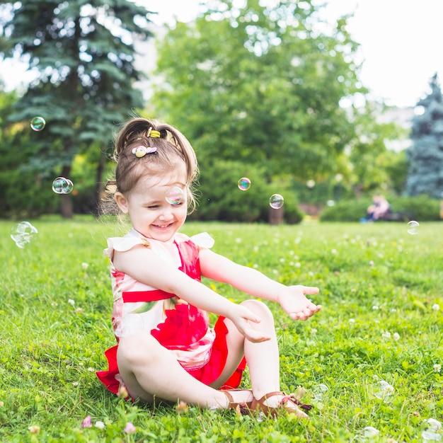 Sourire fille assise sur l'herbe verte jouant avec des bulles transparentes Photo gratuit