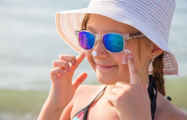 Sourire, fille, à, chapeau, frottis, crème protectrice, visage, plage Photo Premium