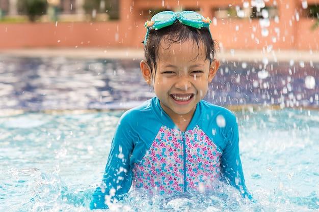 Sourire fille enfant avec des lunettes de protection dans la piscine. Photo Premium