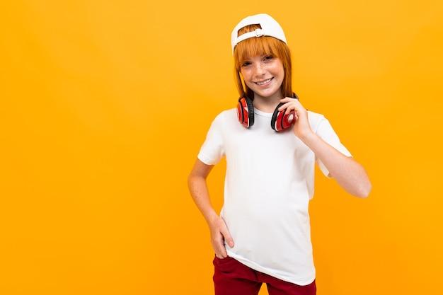 Sourire Fille Rousse Européenne Dans Un T-shirt Blanc Avec Un Casque Photo Premium