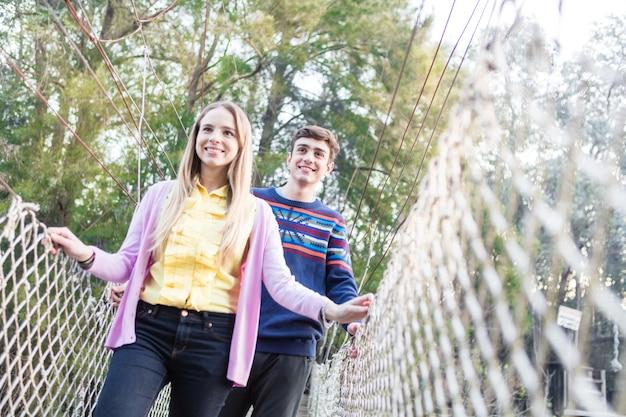 Sourire Fille Traversant Le Pont Avec Son Ami Photo gratuit