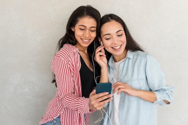 Sourire filles tenant smartphone et écouter de la musique Photo gratuit