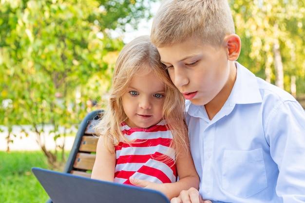 Sourire frère et soeur assis sur un banc dans le parc et jouant sur un ordinateur portable Photo Premium