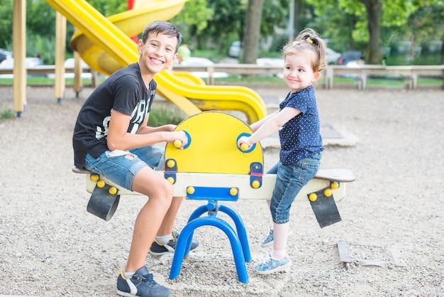 Sourire frère et soeur jouant à la bascule dans la cour de récréation Photo gratuit