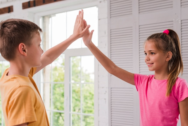 Sourire garçon et fille donnant cinq haut près de la fenêtre Photo gratuit
