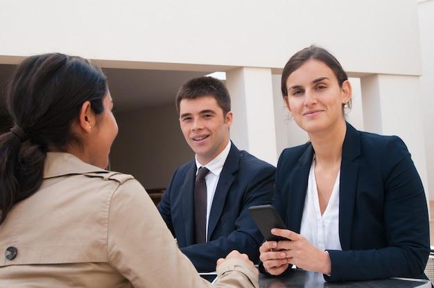 Sourire, gens affaires, et, client, s'asseoir bureau Photo gratuit
