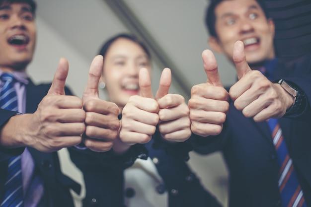 Sourire heureux business célébrant le succès achievement arm raised et montrer pouce levé concep Photo Premium