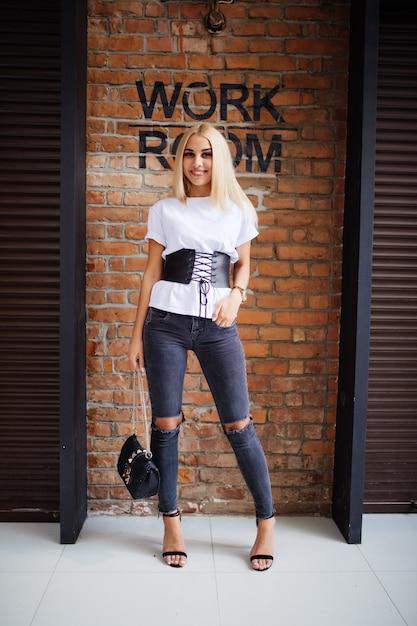 Sourire Heureux Fille Blonde Près De Vieux Mur De Briques Photo gratuit