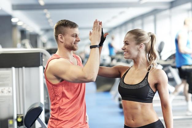 Sourire homme et femme faisant cinq haut dans un gymnase Photo Premium