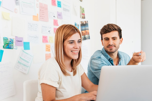 Sourire homme et femme surfer sur internet Photo gratuit