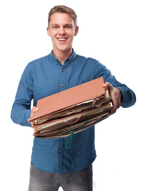 Sourire homme tenant un tas de dossiers de travail Photo gratuit