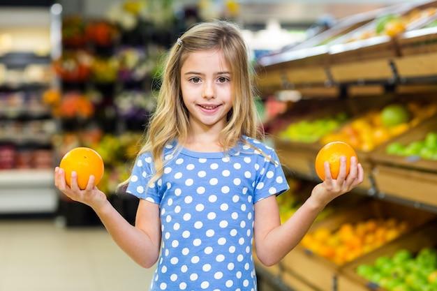 Sourire jeune fille tenant des oranges Photo Premium