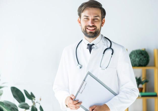 Sourire Jeune Médecin Avec Presse-papiers Photo Premium