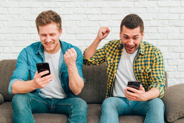 Sourire de jeunes amis de sexe masculin en regardant un téléphone intelligent serrant leur poing Photo gratuit