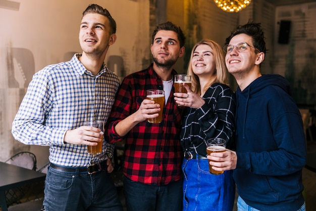 Sourire de jeunes amis tenant les verres de bière en regardant quelque chose Photo gratuit