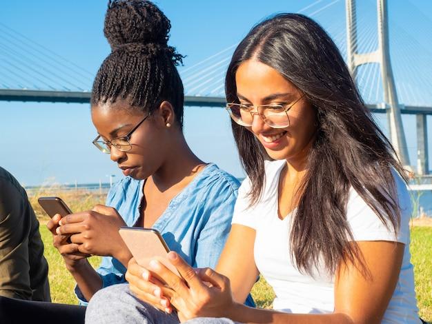 Sourire de jeunes femmes à l'aide de smartphones dans le parc Photo gratuit