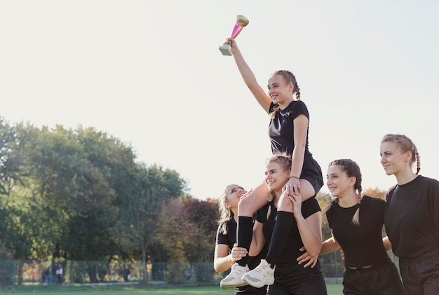 Sourire de jeunes filles remportant un trophée Photo gratuit