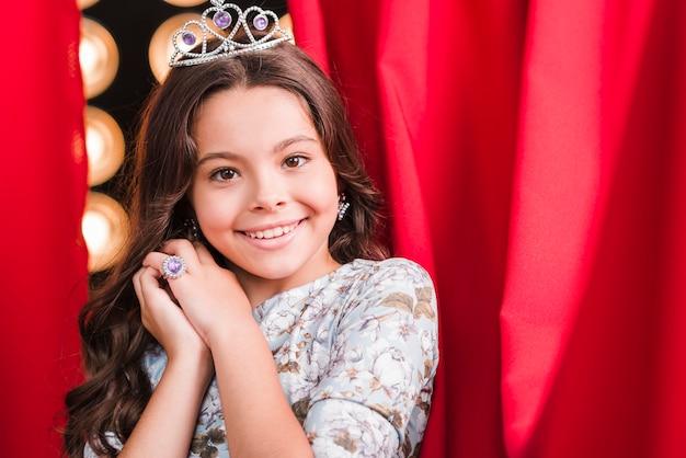 Sourire jolie fille portant la couronne debout devant le rideau rouge Photo gratuit
