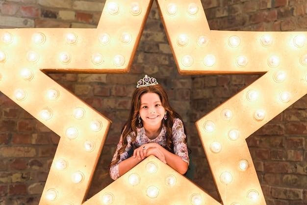 Sourire jolie fille portant s'appuyant sur une étoile brillante contre le mur de briques Photo gratuit