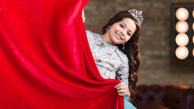 Sourire jolie fille tenant un rideau rouge Photo gratuit