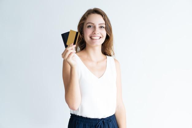 Sourire jolie jeune femme tenant deux cartes en plastique Photo gratuit
