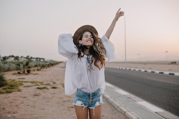 Sourire Joyeuse Femme Aux Cheveux Longs Aux Cheveux Bouclés Respire Une Poitrine Pleine Et Jouit De La Liberté, Debout à Côté De La Route. Portrait D'adorable Jeune Femme En Chemisier Blanc Et Short En Jean S'amuser à L'extérieur Photo gratuit