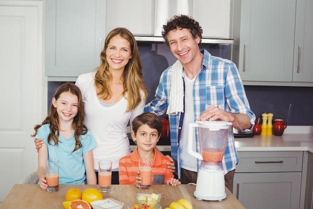 Sourire parents et enfants avec du jus de fruits Photo Premium