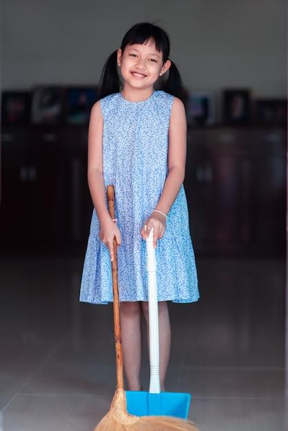 Sourire De Petite Fille Asiatique Balayer Avec Un Balai Et Une Pelle à Poussière Dans La Maison Photo Premium