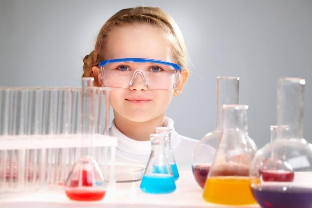 Sourire petite fille avec des ballons pour la chimie Photo gratuit