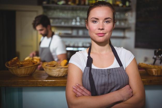 Sourire serveuse debout avec les bras croisés en cafã © Photo gratuit