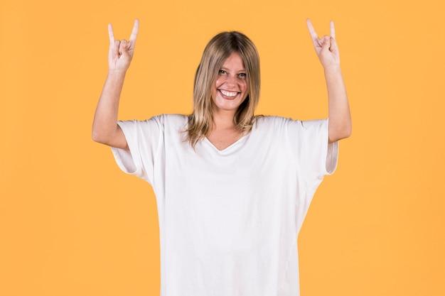 Sourire souriante femme montrant le signe du rocher devant la surface jaune Photo gratuit
